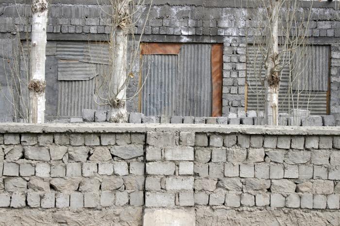 Winterladakh: Graues Haus mit Mauer und Bäumen